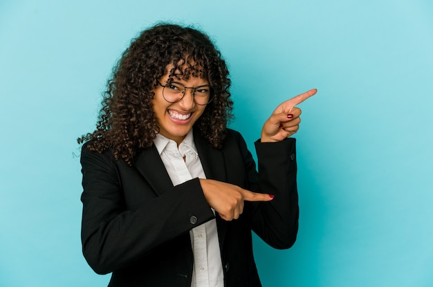 Young african american afro woman isolated excited pointing with forefingers away.