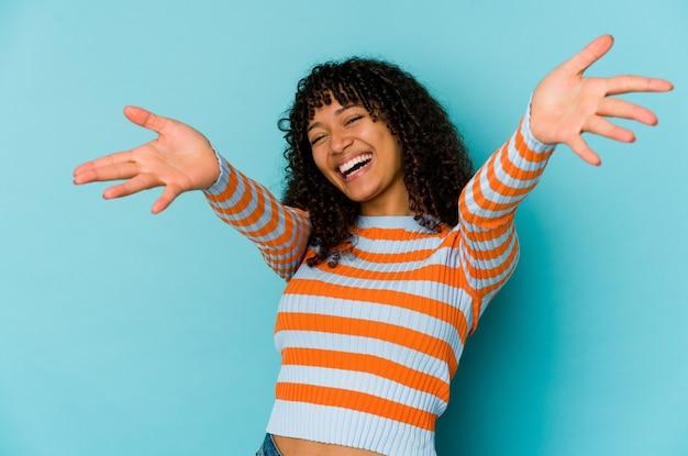 孤立した若いアフリカ系アメリカ人のアフロ女性は抱擁を与えることに自信を持っている