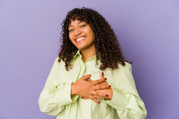 Young african american afro woman isolated has friendly expression, pressing palm to chest. love concept.