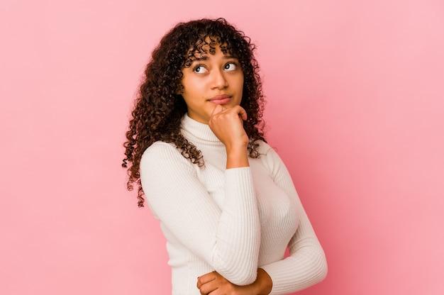 Изолированная молодая афро-американская афро-женщина смотрит в сторону с сомнительным и скептическим выражением лица.