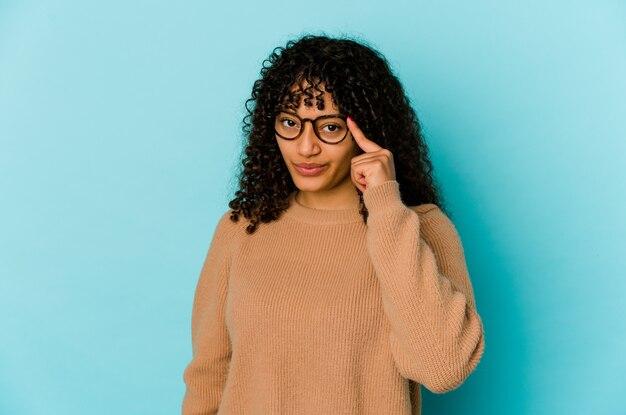 若いアフリカ系アメリカ人のアフロ女性は、タスクに焦点を当て、考え、指でポインティング寺院を分離しました。
