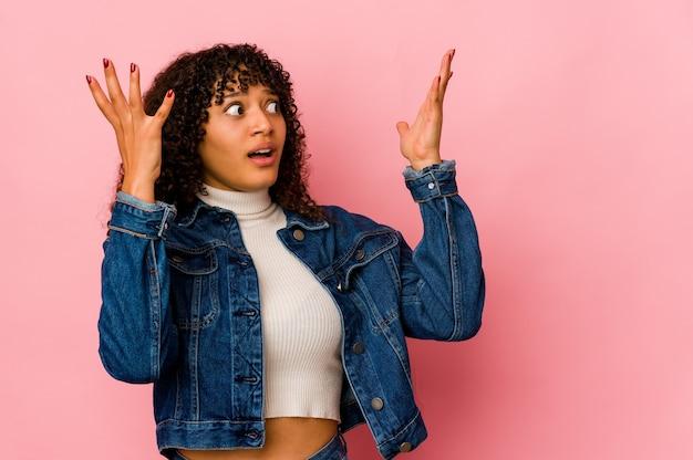 Молодая афро-американская афро-женщина кричала в небо, глядя вверх, разочарованная.