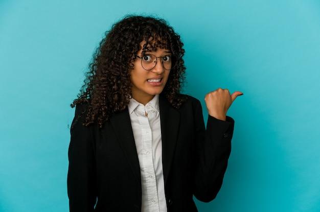 Молодая афро-американская афро-женщина изолирована в шоке, указывая указательными пальцами на пространство для копирования.