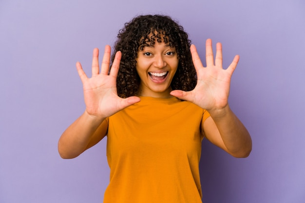 Young african american afro woman isolated showing number ten with hands.