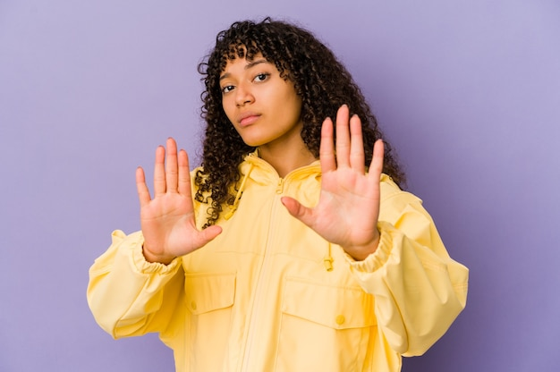 若いアフリカ系アメリカ人のアフロ女性は、一時停止の標識を示している手を伸ばして立って孤立し、あなたを妨げています。