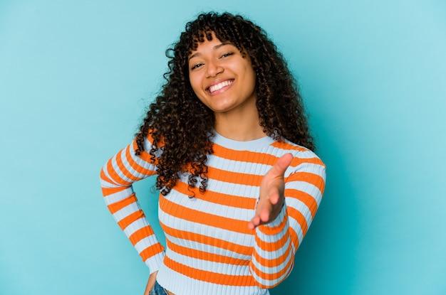 若いアフリカ系アメリカ人のアフロの女性は、挨拶のジェスチャーでカメラでストレッチ手を分離しました。