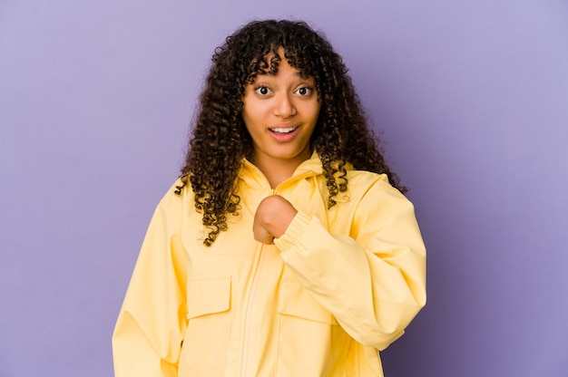 Young african american afro woman isolated surprised pointing with finger, smiling broadly.