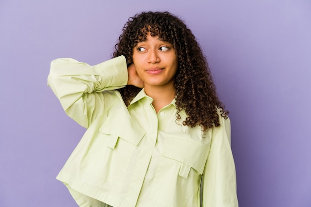 Young african american afro woman isolated touching back of head, thinking and making a choice.