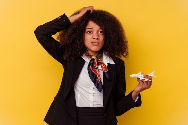 Молодая афро-американская стюардесса, держащая маленький самолет на желтом фоне в шоке, вспомнила важную встречу.