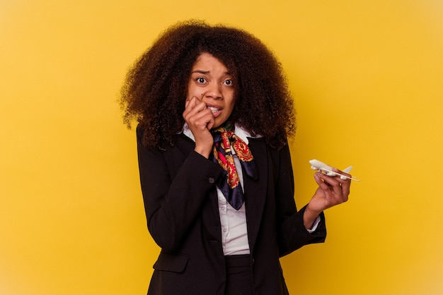 Молодая афро-американская стюардесса держит маленький самолет на желтом фоне, кусает ногти, нервничает и очень тревожится.