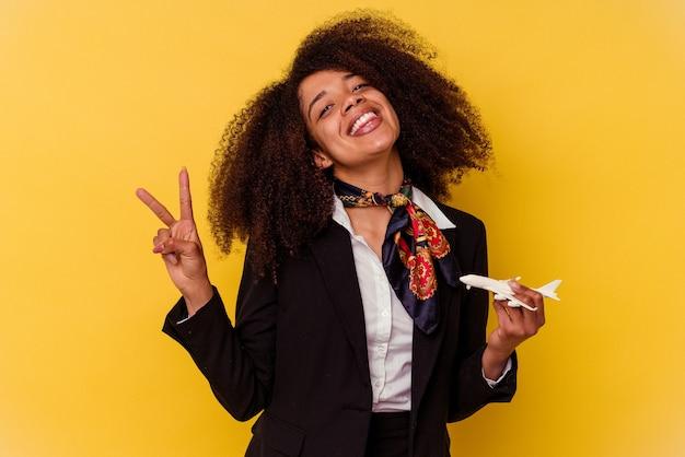 黄色の背景に隔離された小さな飛行機を持っている若いアフリカ系アメリカ人のスチュワーデスは、指で平和のシンボルを示して楽しくてのんきです。