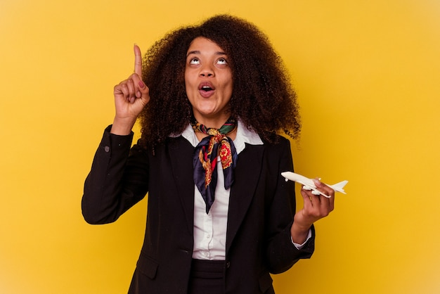 開いた口で逆さまを指している黄色の背景に分離された小さな飛行機を保持している若いアフリカ系アメリカ人のスチュワーデス。
