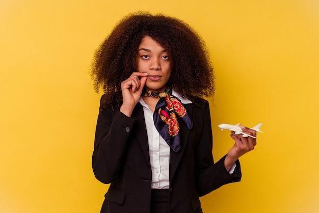 비밀을 유지하는 입술에 손가락으로 노란색 배경에 고립 된 작은 비행기를 들고 젊은 아프리카 계 미국인 스튜 어디 스.