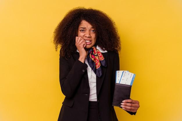 Молодая афро-американская стюардесса держит билеты на самолет, изолированные на желтом фоне, кусая ногти, нервная и очень взволнованная.