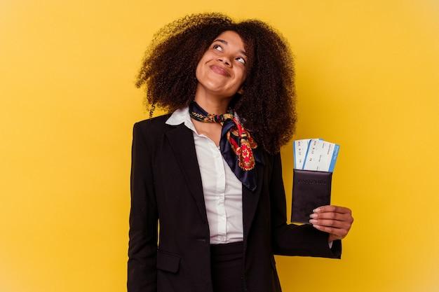 목표와 목적 달성을 꿈꾸는 노란색 배경에 고립 된 비행기 티켓을 들고 젊은 아프리카 계 미국인 스튜어디스