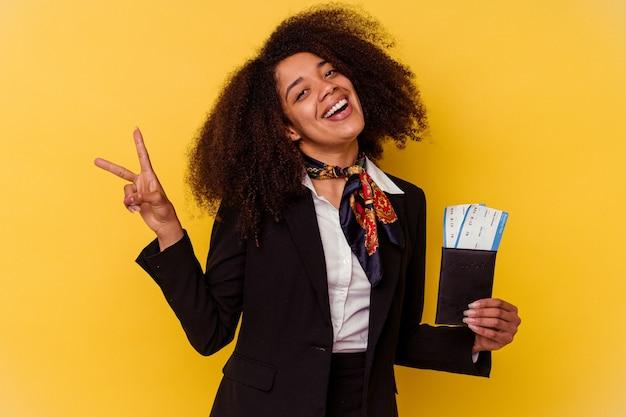黄色の背景に分離された飛行機のチケットを持っている若いアフリカ系アメリカ人のスチュワーデスは、指で平和のシンボルを示して楽しくてのんきです。