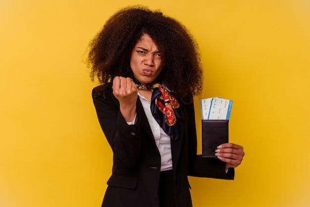 카메라, 공격적인 표정에 주먹을 보여주는 노란색 배경에 고립 된 비행기 티켓을 들고 젊은 아프리카 계 미국인 스튜 어디 스.