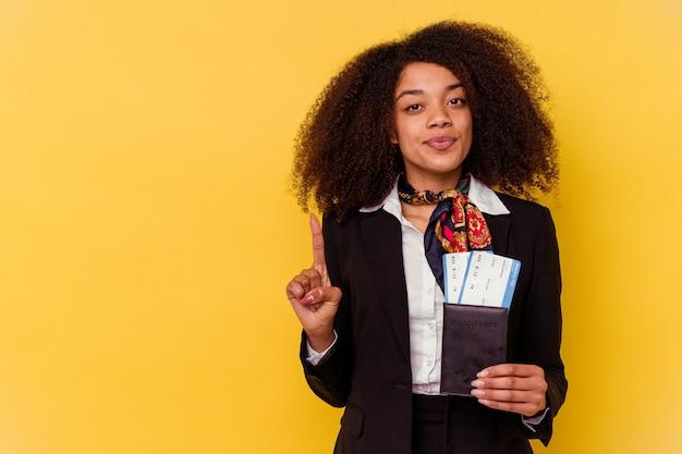 손가락으로 번호 하나를 보여주는 노란색 배경에 고립 된 비행기 티켓을 들고 젊은 아프리카 계 미국인 스튜 어디 스.