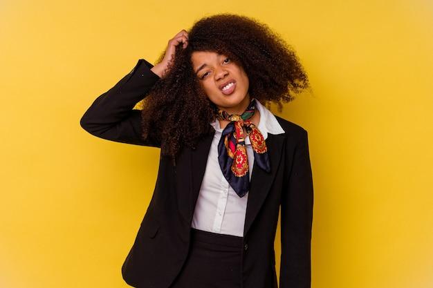 충격을 받고 노란색 배경에 고립 된 젊은 아프리카 계 미국인 스튜어디스, 그녀는 중요한 회의를 기억했습니다.