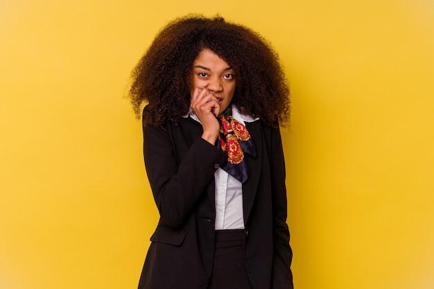 Молодая афро-американская стюардесса изолирована на желтом фоне, кусая ногти, нервная и очень взволнованная.