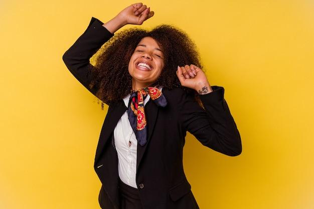 특별 한 날을 축 하하는 노란색 배경에 고립 된 젊은 아프리카 계 미국인 스튜 어디 스 점프 하 고 에너지로 팔을 올립니다.