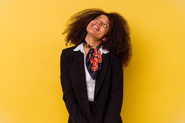 목표와 목적 달성을 꿈꾸는 노란색 배경에 고립 된 젊은 아프리카 계 미국인 스튜어디스