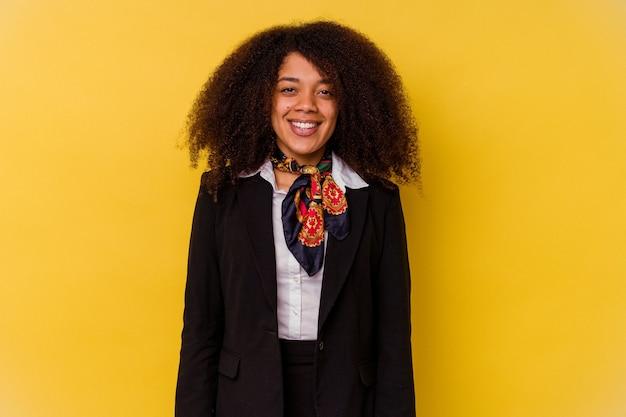 행복 하 고 웃 고 쾌활 한 노란색 배경에 고립 된 젊은 아프리카 계 미국인 스튜 어디 스.