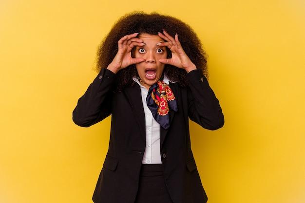 성공 기회를 찾기 위해 눈을 유지하는 노란색 배경에 고립 된 젊은 아프리카 계 미국인 스튜 어디 스.