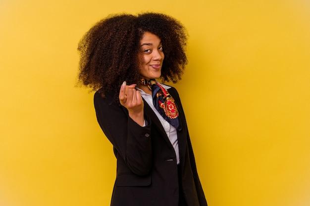 黄色の背景に孤立した若いアフリカ系アメリカ人のスチュワーデスが、誘うように指であなたを指さします。