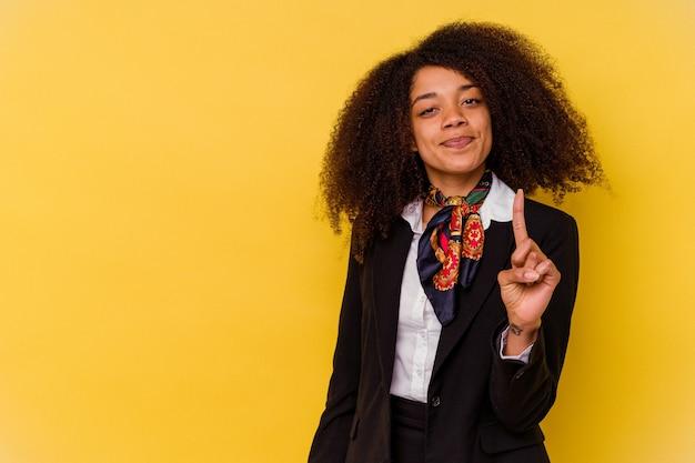 손가락으로 번호 하나를 보여주는 노란색 배경에 고립 된 젊은 아프리카 계 미국인 스튜 어디 스.