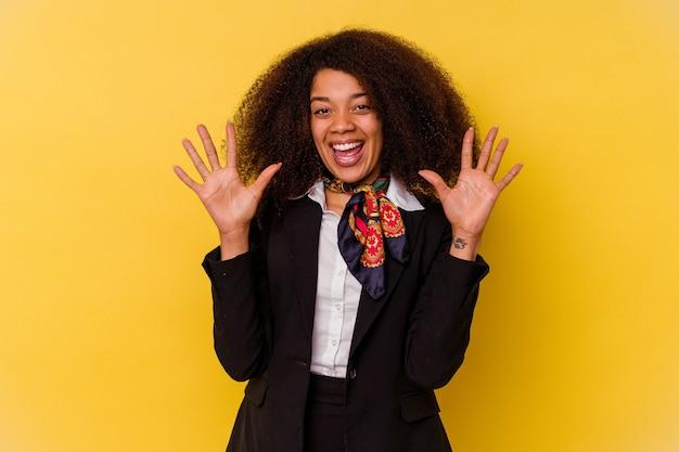 若いアフリカ系アメリカ人の空気のホステスは、手で 10 番を示す黄色の背景に分離されました。