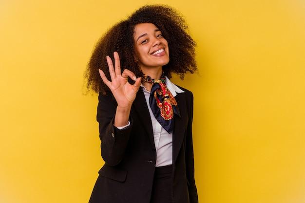 黄色の陽気で自信に満ちたジェスチャーで孤立した若いアフリカ系アメリカ人のエアホステス。