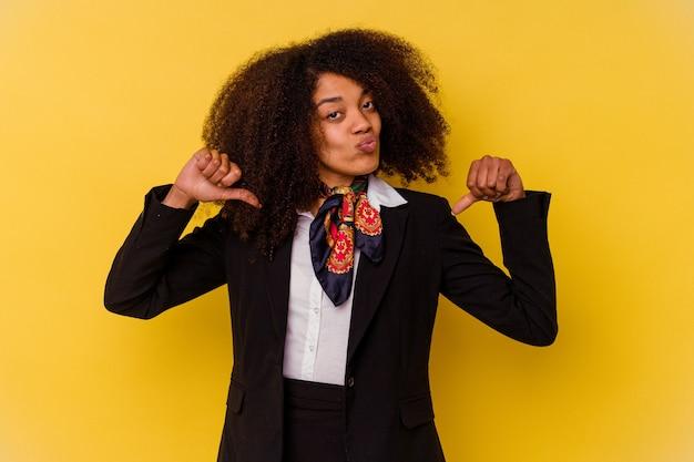 노란색에 고립 된 젊은 아프리카 계 미국인 스튜어디스는 자부심과 자신감을 느낍니다.