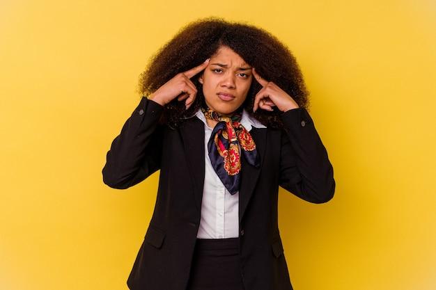 黄色で隔離された若いアフリカ系アメリカ人のエアホステスは、人差し指を頭に向けたまま、タスクに集中しました。