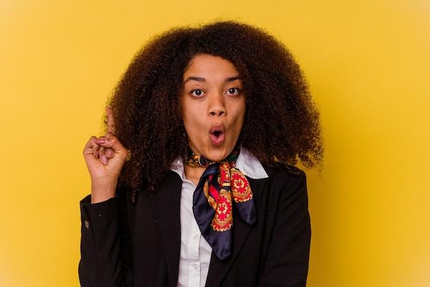 いくつかの素晴らしいアイデア、創造性の概念を持っている黄色で隔離された若いアフリカ系アメリカ人のエアホステス。