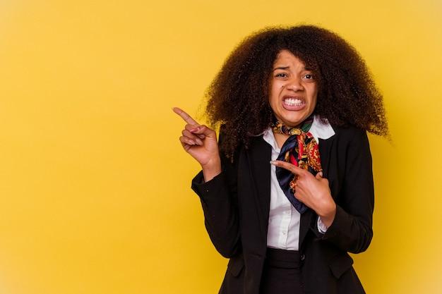 노란색에 고립 된 젊은 아프리카 계 미국인 스튜 어디 스 복사본 공간을 검지 손가락으로 가리키는 충격.