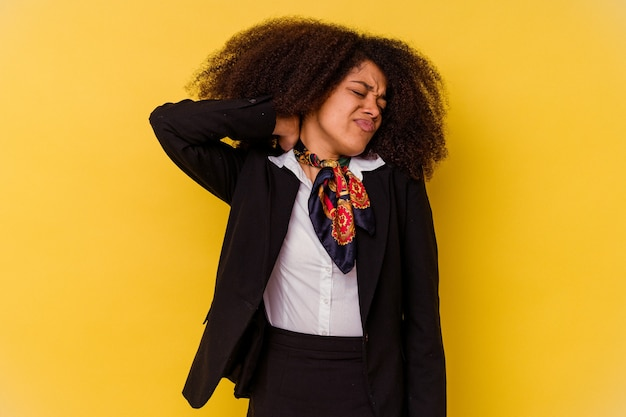 Молодая афроамериканская стюардесса изолирована на желтом и страдает от боли в шее из-за малоподвижного образа жизни.