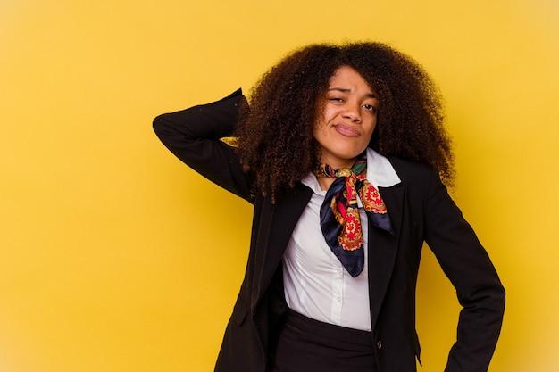 생각 하 고 선택을 하 고 머리를 다시 만지고 노란색 벽에 고립 된 젊은 아프리카 계 미국인 스튜 어디 스.