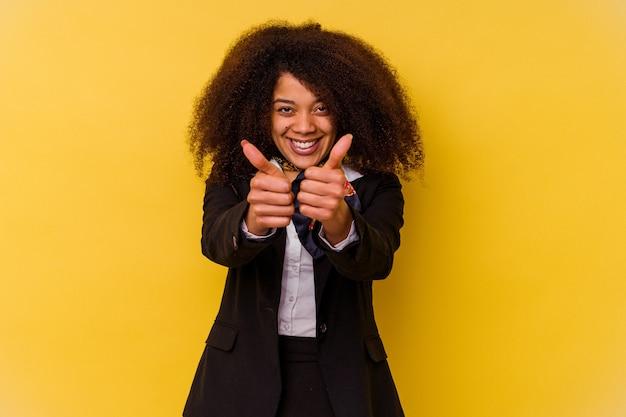 엄지 손가락으로 노란색에 고립 된 젊은 아프리카 계 미국인 스튜어디스, 뭔가에 대한 건배, 지원 및 존중 개념.