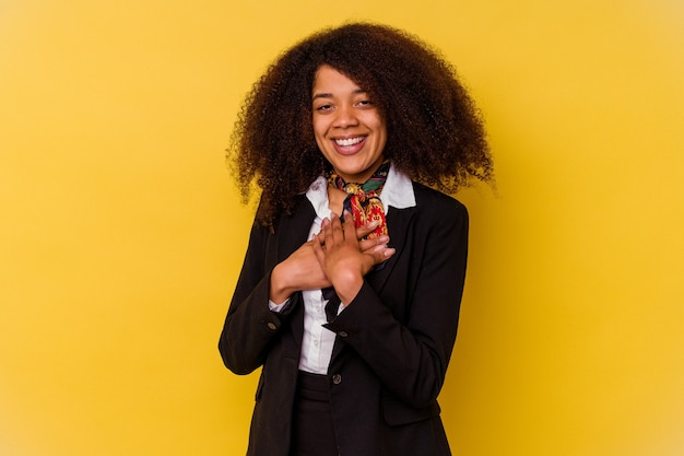 Young african american air hostess isolated on yellow has friendly expression, pressing palm to chest. love concept.