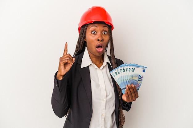 Молодая афро-американская женщина архитектора, держащая счета, изолированные на белом фоне, имея идею, концепцию вдохновения.