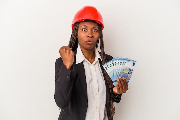 카메라에 주먹을 보여주는 흰색 배경에 고립 된 지폐를 들고 젊은 아프리카 계 미국인 건축가 여자, 공격적인 표정.