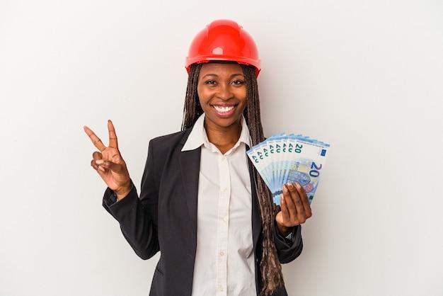 指で2番目を示す白い背景で隔離の請求書を保持している若いアフリカ系アメリカ人建築家の女性。