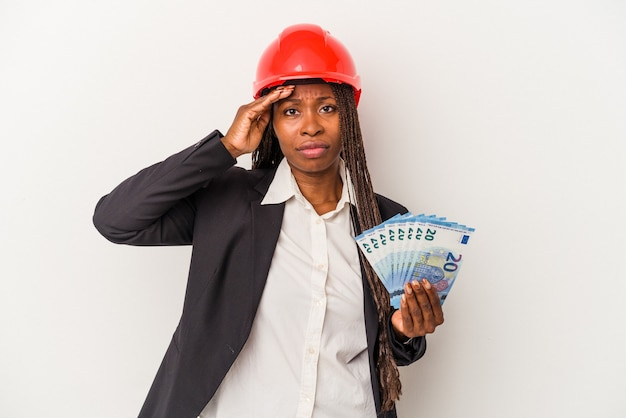 Young african american architect woman holding bills isolated on white background being shocked, she has remembered important meeting.