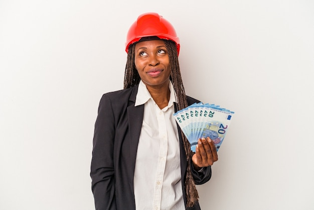 Young african american architect woman holding bills isolated on white background dreaming of achieving goals and purposes