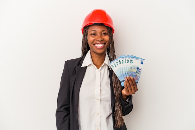 Young african american architect woman holding bills isolated on white background happy, smiling and cheerful.