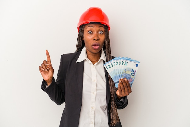 Young african american architect woman holding bills isolated on white background having some great idea, concept of creativity.