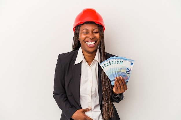 Young african american architect woman holding bills isolated on white background laughing and having fun.