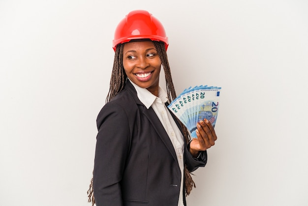 Young african american architect woman holding bills isolated on white background looks aside smiling, cheerful and pleasant.