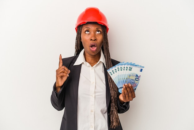 Young african american architect woman holding bills isolated on white background pointing upside with opened mouth.